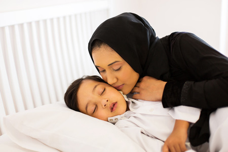 caring muslim mother kissing baby boy while he is asleep