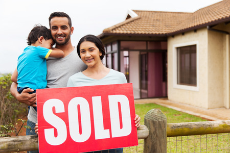 indian family standing outside their house and holding sold sign Stock Photo