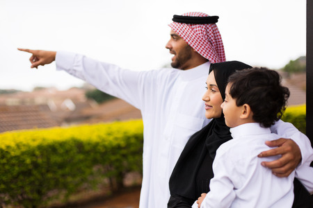family outside: happy muslim family outside their home pointing Stock Photo