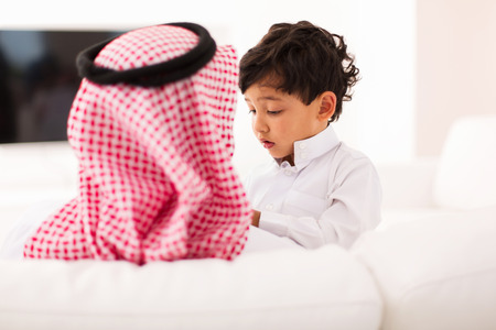 arab men: little muslim boy and his father spending time together at home