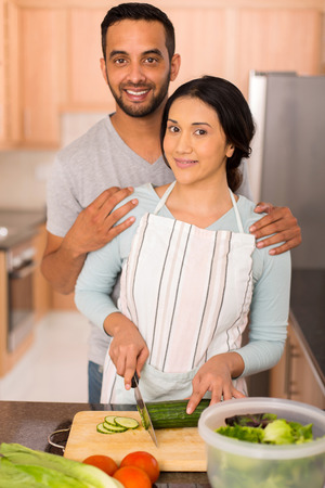 wedded: beautiful indian couple cooking together in home kitchen
