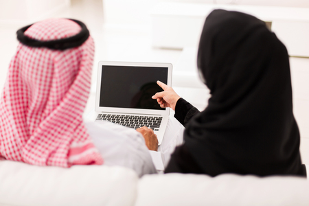 back home: back view of muslim couple pointing at laptop screen