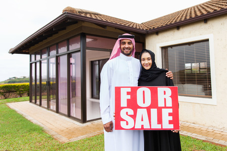 house family: portrait of lovely muslim couple holding for sale sign in front of their house Stock Photo