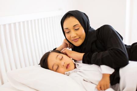 madre e figlio: bella madre musulmana guardando il suo figlio dormire nel letto