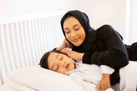 petite fille musulmane: belle mère musulmane regardant son fils dormir dans le lit