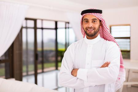 good looking guy: portrait of happy arabian man standing indoors Stock Photo