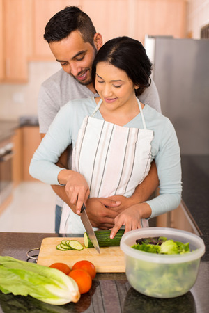 indian cooking: lovely young indian couple chopping vegetables together in the kitchen