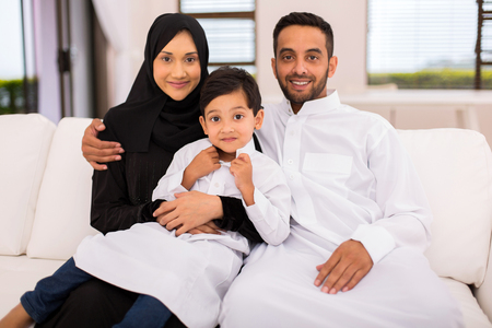 happy muslim family sitting on the couch at home