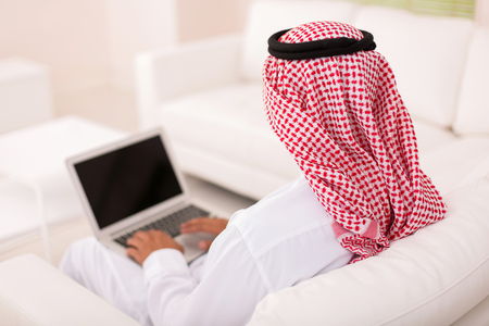 back view of man: rear view of muslim man sitting on sofa using laptop Stock Photo