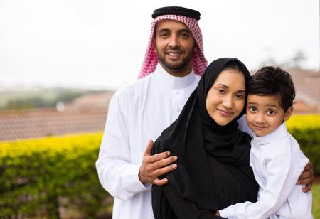 幸せの若いイスラム教徒の家族は屋外の肖像画