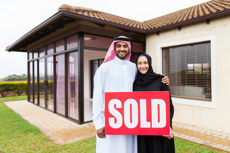 real estate sold: happy arabian couple  in front of new home with sold real estate sign Stock Photo