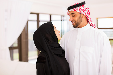 middle eastern clothing: happy arabian couple looking at each other at home Stock Photo