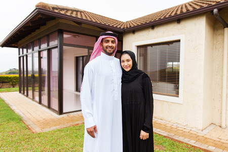 middle eastern families: portrait of lovely young muslim couple standing in front of their house