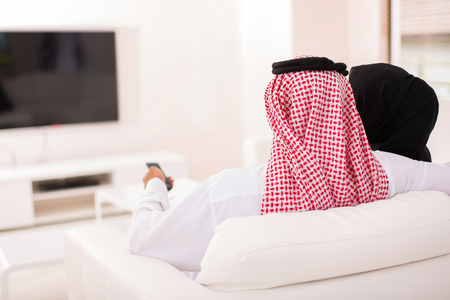 middle eastern woman: rear view of muslim couple watching tv at home