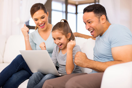 cheerful family looking at laptop screen