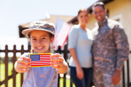 military uniform: little girl holding american flag badge in front of parents Stock Photo