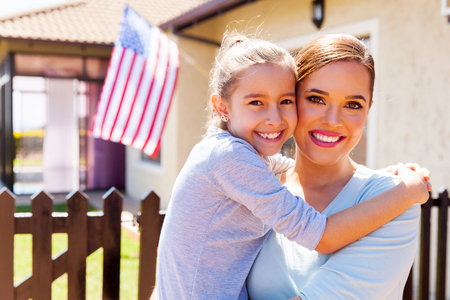 happy mother and daughter with american flag outside their house