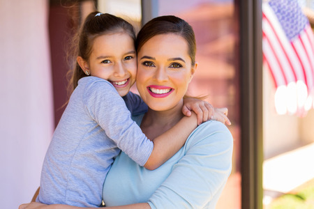 american house: pretty little american girl hugging her mother Stock Photo