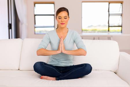 Donna pacifica che fa la meditazione di yoga a casa