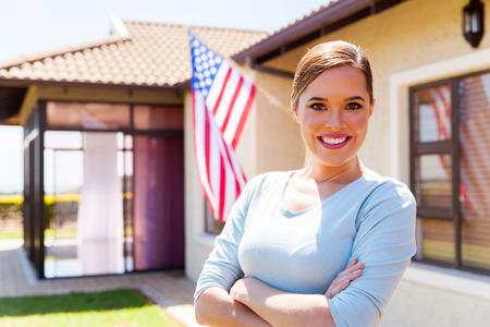 banderas america: americanos mujer con los brazos cruzados frente a su casa Foto de archivo