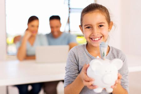 Fröhliche kleine Mädchen mit den Eltern im Hintergrund hält Sparschwein Standard-Bild - 50864676