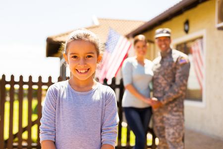 家庭: 可愛的小女孩站在父母面前戶外