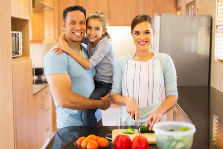 preparation: pretty woman making salad for family in home kitchen