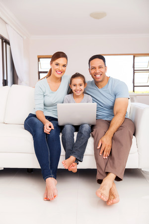 beautiful family using laptop computer in living room photo