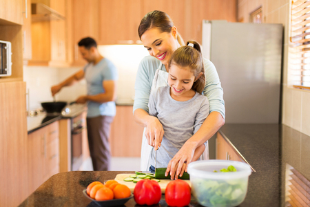 lovely young family preparing meal in kitchen photo