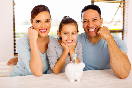 cheerful family of three with piggybank at home