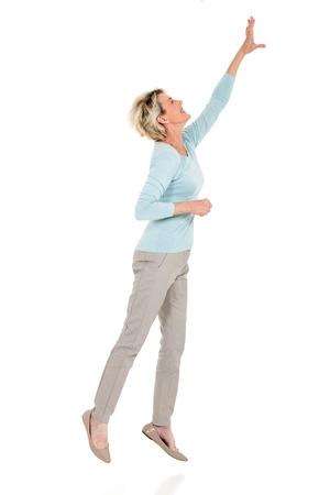 アクティブなシニア女性までジャンプし、白い背景に手を差し伸べる
