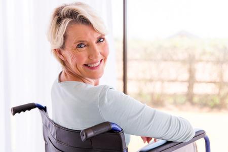 persona en silla de ruedas: mujer con discapacidad en silla de ruedas feliz mirando hacia atrás Foto de archivo