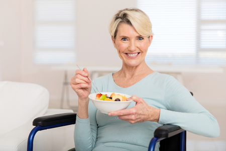 woman diet: portrait of cute mature woman in wheelchair eating fruit salad