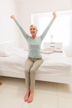 smiling middle aged woman sitting on bed and stretching