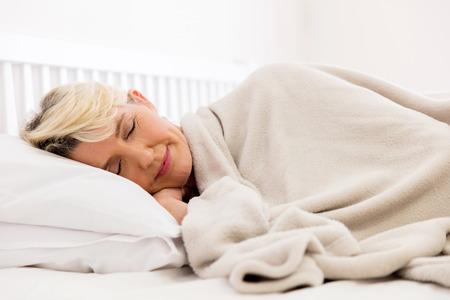かなり年配の女性がベッドで寝ています。