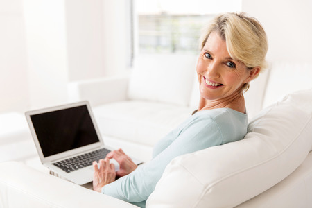 mid age: cheerful mid age woman with laptop computer at home