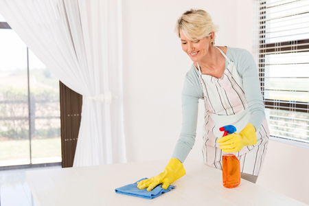 wiping: pretty senior housewife wiping table at home Stock Photo