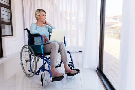wheel house: disabled senior woman with laptop relaxing at home Stock Photo