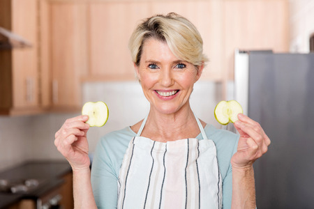 eating salad: happy senior woman holding slices of apple in kitchen