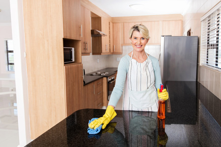 desk tidy: smiling mid age housewife cleaning the kitchen