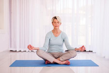 peaceful senior woman meditating at home