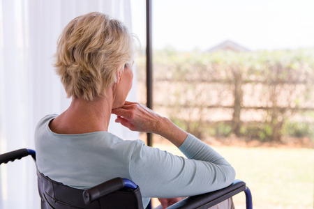 back view of handicapped senior woman looking through window