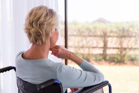 Zadní pohled na postiženou starší ženy dívat se skrz okno Reklamní fotografie