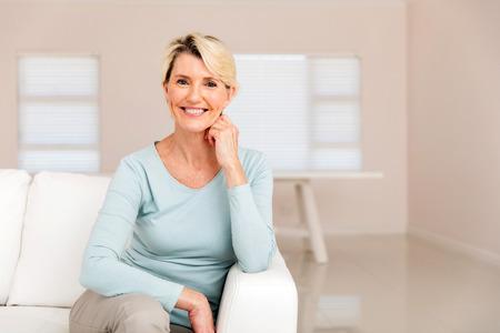 Portrait eines glücklichen Frau mittleren Alters sitzt auf dem Sofa