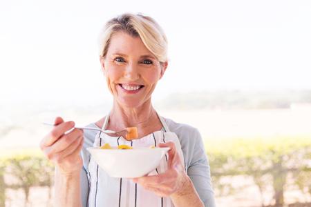 felice di mezza età donna mangiare insalata a casa