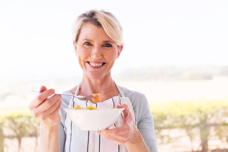 woman eating fruit: happy middle aged woman eating salad at home Stock Photo