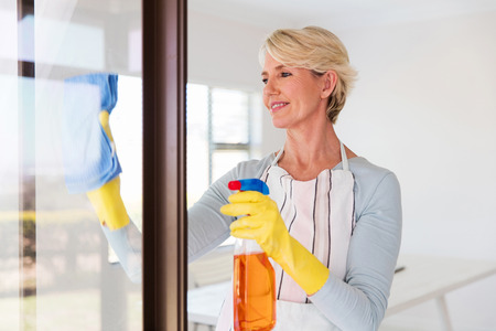 contemporary house: beautiful senior woman cleaning window glass