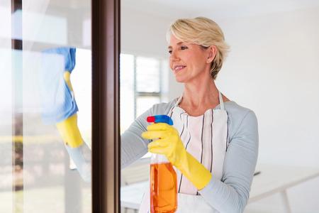 orden y limpieza: hermoso cristal de la ventana de limpieza de la mujer mayor