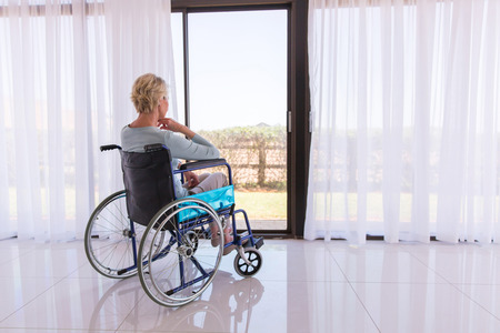 thoughtful disabled woman in wheelchair looking through door glass