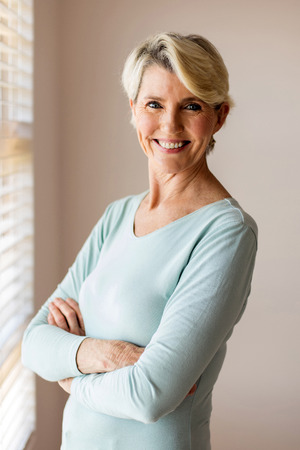 arms folded: portrait of happy senior woman with arms folded at home
